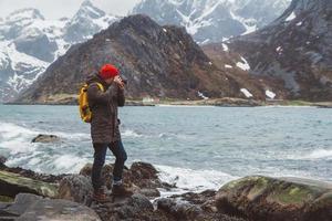 photographe de voyageur sur les rochers sur fond de mer et de montagne photo