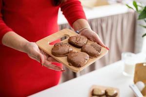 femme en robe rouge faisant des biscuits de la Saint-Valentin à la cuisine photo