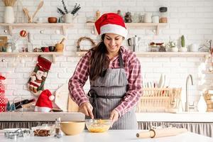 Jeune femme latine en fouettant les œufs la cuisson à la cuisine photo