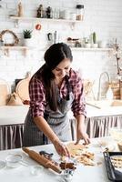 Jeune femme brune préparant des biscuits à la cuisine photo