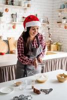 jeune femme latine versant de la farine à la cuisson de la pâte à la cuisine photo