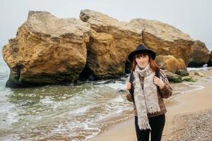 femme dans un chapeau avec un sac à dos sur fond de mer et de rochers photo