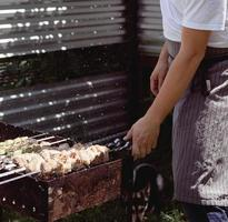 gros plan de brochettes sur des brochettes, homme grillant de la viande à l'extérieur photo