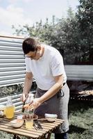 Jeune homme grillant des brochettes sur des brochettes, homme grillant de la viande à l'extérieur photo