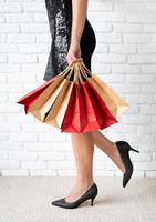 Jambes de femme avec des sacs sur fond blanc photo
