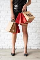 jambes de femme avec des sacs à provisions, texte du vendredi noir sur un sac en papier photo