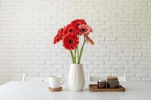 marguerites gerbera lumineuses dans un vase blanc sur une table de cuisine, style minimaliste photo