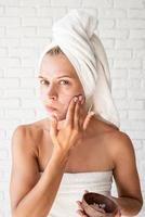 femme préoccupée dans des serviettes de bain blanches appliquant un gommage sur son visage photo