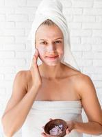 Jeune femme de race blanche portant des serviettes blanches appliquant un gommage sur son visage photo