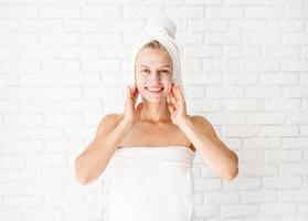 heureuse jeune femme souriante appliquant un gommage sur son visage et son cou photo