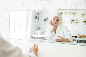 heureuse jeune femme appliquant un gommage sur son visage photo