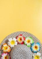 chapeau d'été avec des fleurs de plumeria sur fond jaune photo