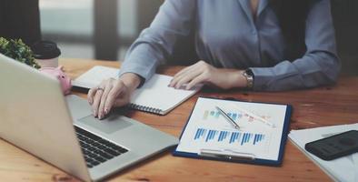 femme d'affaires vérifiant les bénéfices déclarés sur le papier et l'ordinateur portable. photo