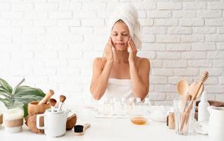 femme appliquant de la crème sur la peau de son visage faisant des procédures de spa photo