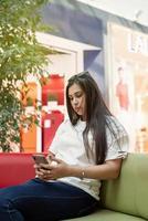femme assise sur le canapé dans le centre commercial, regardant le téléphone photo