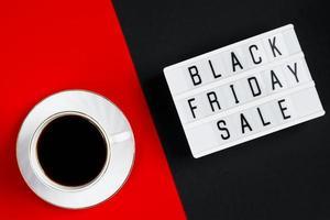 concept de vente du vendredi noir. tasse de café sur fond rouge. photo