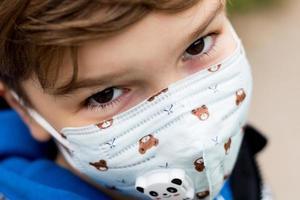gros plan d'un enfant portant un masque facial kn95 en raison de la pandémie de coronavirus. photo