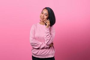 femme asiatique surprise lors de la réception d'un appel entrant sur smartphone photo