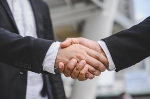 les gens d'affaires se serrent la main pour conclure un accord de proposition commerciale photo