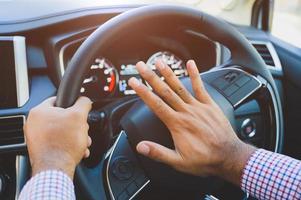 homme de main poussant le klaxon de voiture tout en conduisant la voiture. photo