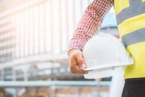 ingénierie tenant un casque de sécurité sur fond de bâtiment. photo