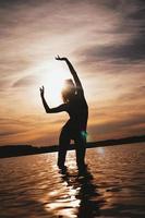 femme insouciante heureuse appréciant le beau coucher de soleil sur la plage photo