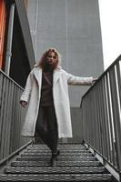 une fille aux cheveux bouclés rouges dans un manteau blanc pose sur les escaliers du parking photo