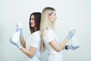 deux femmes tiennent un vaporisateur - antiseptique ou détergent comme des armes à feu photo