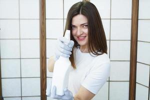 une femme tient un vaporisateur - antiseptique ou détergent comme des armes à feu photo