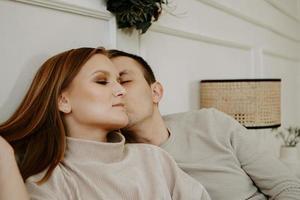 joli couple d'amoureux au lit ensemble. ils s'embrassent et sourient photo