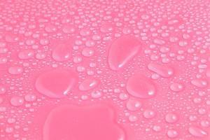 gros plan gouttes d'eau sur fond rose photo