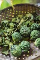 Fruits frais de lime kaffir thaï et feuilles séchées dans un panier d'ingrédients rustiques photo