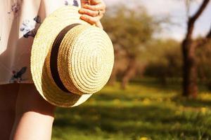 photo en gros plan - fille dans un chapeau de paille tenant un chapeau dans ses mains