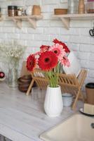 Marguerites gerbera rouges et roses dans un vase blanc sur une cuisine en bois photo