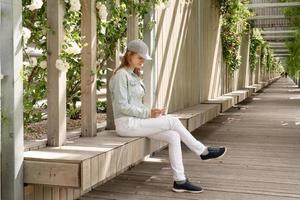 femme assise sur le banc en bois à l'aide de téléphone dans l'allée du parc verdoyant photo