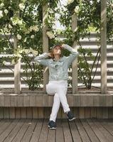 femme assise sur le banc en bois dans l'allée du parc verdoyant photo