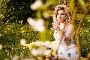 Belle jeune femme aux cheveux blonds au chapeau de paille boit du vin photo