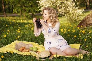 femme avec du raisin lors d'un pique-nique dans le jardin d'été photo