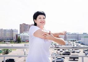 femme âgée souriante faisant des étirements à l'extérieur sur fond urbain photo