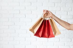 main de femme avec des sacs à provisions, texte du vendredi noir sur un sac en papier photo