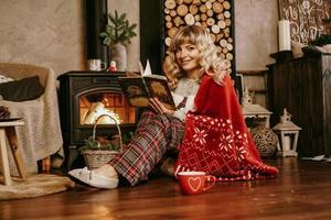 Happy young woman reading book devant l'intérieur de Noël photo