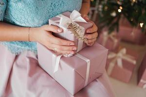 mains tenant le cadeau présent. gros plan des mains féminines donnant le cadeau photo