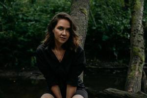 jeune femme - portrait proche dans une forêt sombre. femme en chemise noire photo