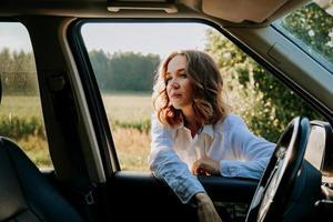 femme à la fenêtre de la voiture. déplacements hors de la ville. concept de voyage et de joie photo