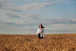 femme court dans un champ de blé un jour d'été. concept de bonheur et de joie photo