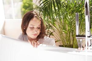 penser positivement. la femme attend que la baignoire soit remplie d'eau photo