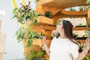 femme assise sur le canapé dans le centre commercial, regardant les plantes photo