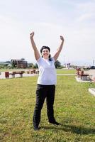 femme aînée, dans, sports vêtements, exercisme, dans parc, debout, à, haut photo