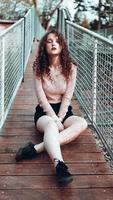 portrait de mode d'une jeune femme branchée assise près du filet rabitz photo