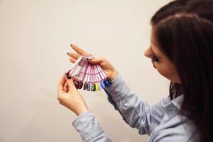 la fille choisit la couleur du vernis pour la manucure. testeurs ongles photo